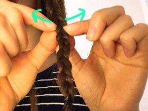 三つ編みを指で緩めている写真